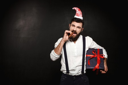 Young handsome man holding christmas gift box over black background. Copy space. Stock Photo