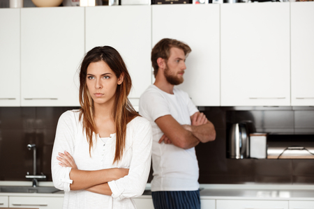 Displeased young beautiful brunette girl in quarrel with her boyfriend background at home.