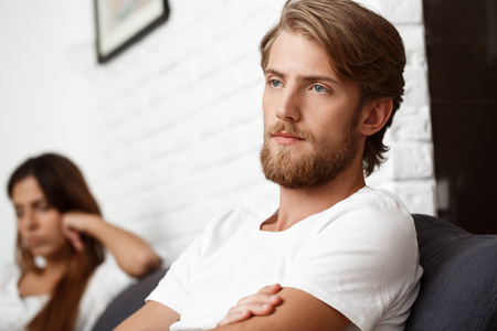 ignore: Upset young handsome man in quarrel with his girlfriend on sofa background. Stock Photo