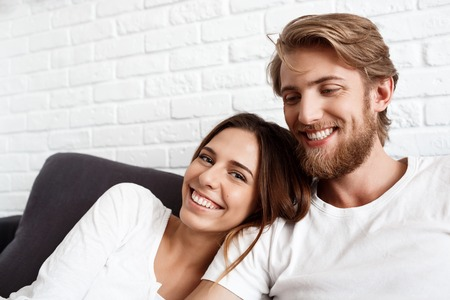 sincere girl: Portrait of young beautiful couple smiling looking at camera sitting on sofa. Stock Photo