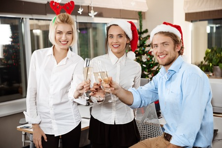 Colleagues celebrating christmas party in office drinking champagne smiling looking at camera. Copy space. Stock Photo