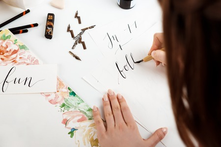 Girl writing calligraphy on postcards. Art design. Copy space. Imagens
