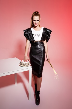 leather skirt: Young beautiful brutal blonde girl in black leather skirt push hand in cake holding sparkler over pink background.