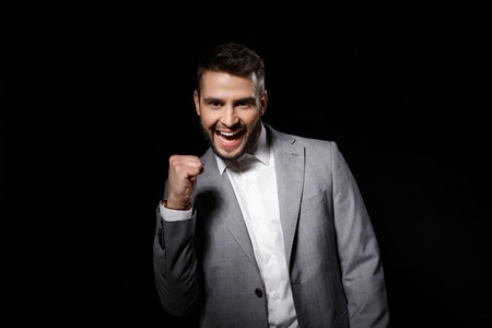 Young successful businessman rejoicing isolated on black background. Copy space. Stock Photo