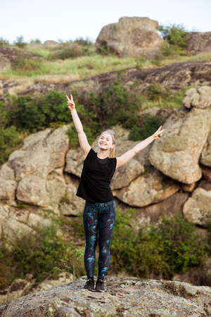 Sportive girl smiling, showing peace, standing on rock in canyon.