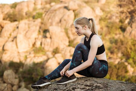 Young sportive girl tying shoelaces, sitting on rock in canyon.