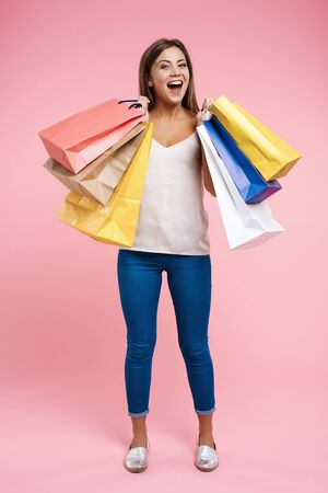 Happy young woman holding shopping bags staying on pink background