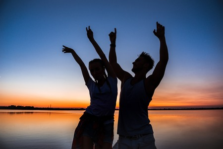 Silhouettes of young beautiful couple resting rejoicing at sunrise near lake. Stock Photo
