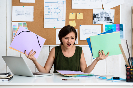 architector: Upset young beautiful businesswoman sitting at workplace. Office background. Stock Photo