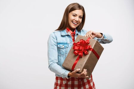 uncovering: Attractive young woman uncovering present box looking glad and smiling