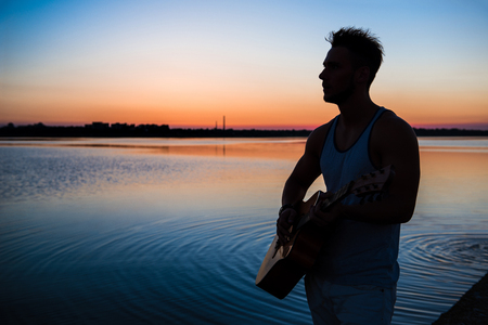 Silhouette of young handsome man playing guitar at seaside during sunrise. Outdoors. Stock Photo