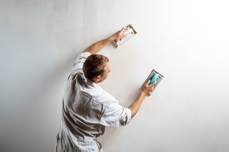 Worker grinding white wall with sandpaper. Copy space.