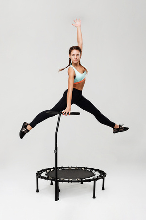Sporty woman training on rebounder getting ready for competition