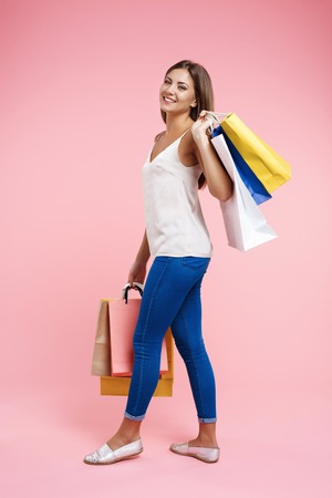 Sideview of smiling young woman walking with colorful shopping bags