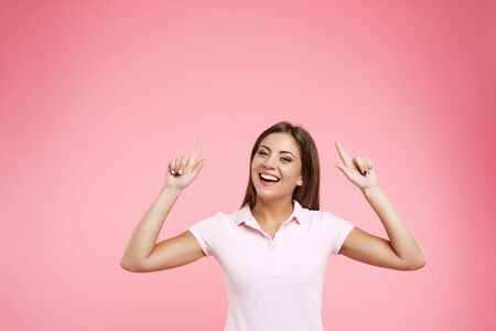 portait: Portait of woman in pink polo posing with hands up