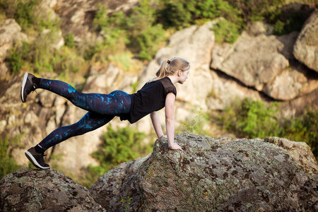 Beautiful sportive blonde girl stretching on rock in canyon.