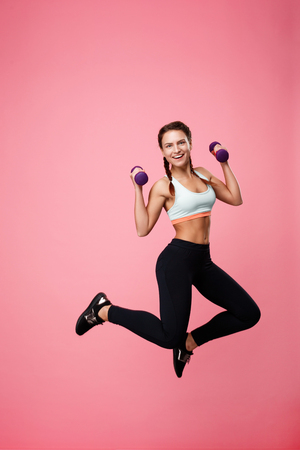 Young excited woman jumping up with purple dumbbells looking straight Stock Photo