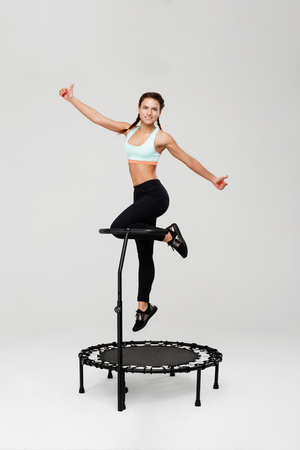 Woman on rebounder jumping up showing thumbs up with smile