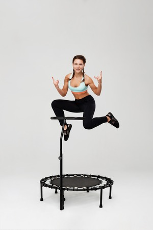 Sporty girl training on rebounder and showig rock sign Foto de archivo