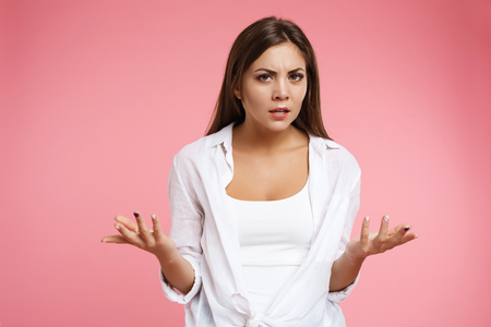 Nice girl doesn t understand what s going on waving hands Stock Photo