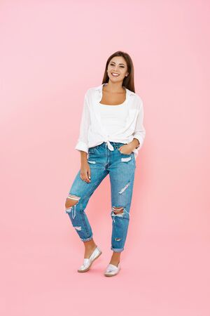 Woman in trendy spring outfit. Blue jeans and white shirt Stock Photo