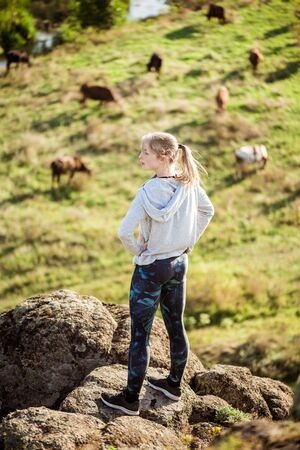 Beautiful sportive girl standing on rock. Field with cows background.