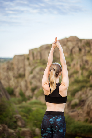 Young sportive girl training yoga asanas on rock in canyon. Stock Photo
