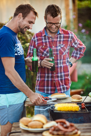 Young men roasting barbecue on grill in cottage countryside. Stock Photo - 74208460