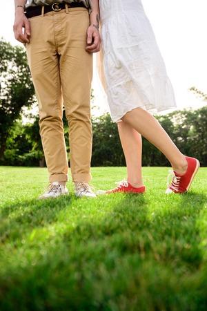 pies bonitos: Ciérrese para arriba de las piernas de los pares en keds en hierba. Foto de archivo
