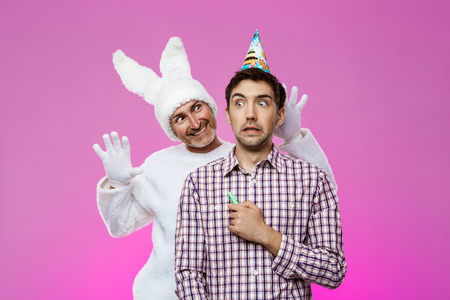 hallucinations: Rabbit frightening drunk man over purple background. Birthday party. Stock Photo