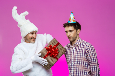 hallucinations: Rabbit giving birthday gift to drunk man over purple background. Stock Photo