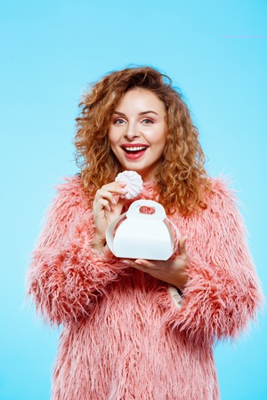Close up portrait of cheerful smiling beautiful brunette curly girl in pink fur coat eating marshmallow over blue background. Copy space.