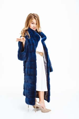 Girl in long fur coat, white midi dress, beige heels shoes posing with hand up.