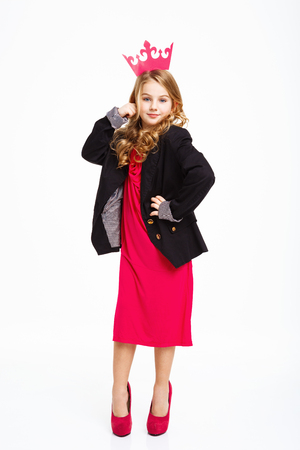Girl with right hand on head, left hand on hip, posing in mothers clothig.