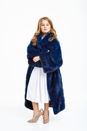 Nice girl in mothers fake fur coat with hands across, pretending to be adult.