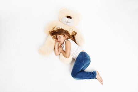 Top view of cute kid in white shirt and blue jeans sleeping on favourite toy. Stock Photo