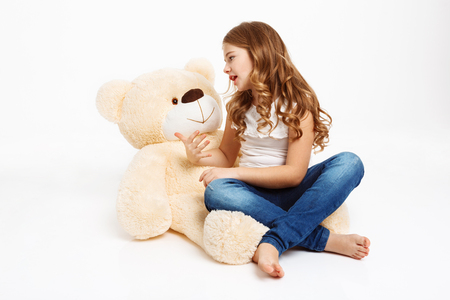 Beatiful curly girl sitting on floor with beige toy bear, telling story. White background.