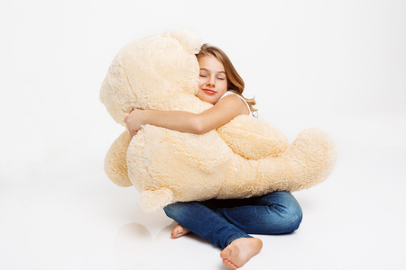 Cheerful kid sitting on floor holding toy bear on knees, hugging it with eyes closed. Stock Photo
