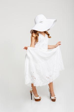 Zijaanzicht van het meisje in mooie zomer kleding, stak kanten jurk. Witte achtergrond.