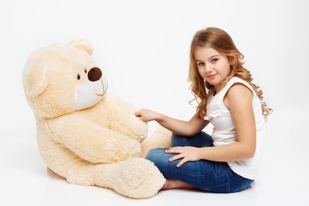Beautiful girl sitting on floor with toy bear holding his paw, looking at camera.