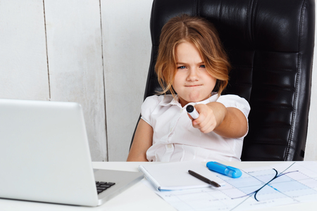 biz: Young beautiful girl looking and  pointing felt pen to camera, sitting at working place in office.