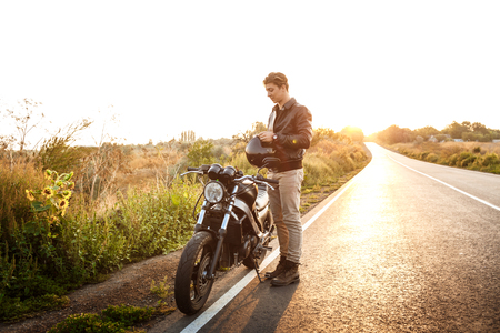 Young handsome man in leather jacket posing near his motorbike at countryside road.