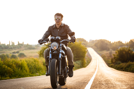 Young handsome man in leather jacket riding on motorbike at countryside road.