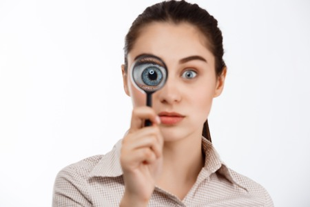 Young beautiful brunette girl looking at camera through magnifier over white background. Stock Photo