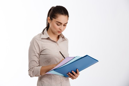Surprised young beautiful businesswoman holding colorful folders over white background Stock Photo