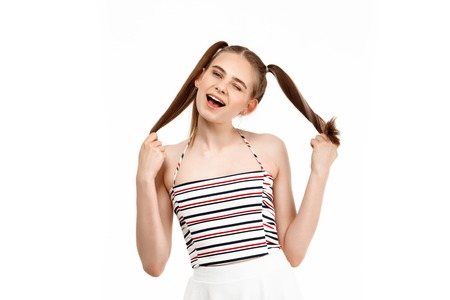 Young pretty girl winking, smiling, looking at camera, isolated on white background. Copy space.