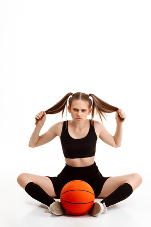 Young emotional pretty girl posing with basketball over white background. Copy space.