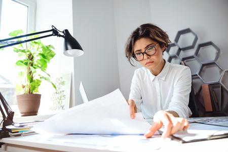 biz: Young beautiful businesswoman in glasses sitting at workplace in office.