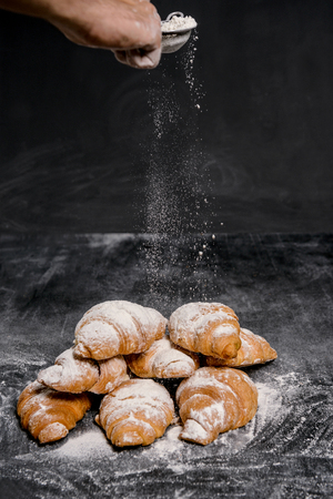 Picture of croissants with powdered sugar on grey table. Macro. Stock Photo