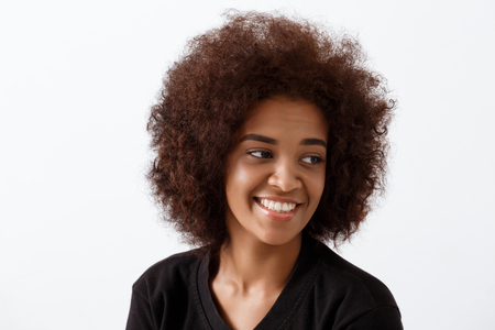 Young beautiful african girl smiling over light background. Copy space. Imagens